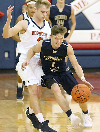 (Brad Davis/The Register-Herald) Greenbrier West's Noah Midkiff shields the ball from Independence defender Ethan Testerman as he breaks up the court Friday night in Coal City.