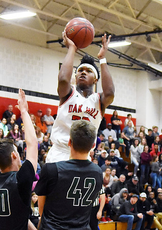Oak Hill's Andrew Work (23) gets a shot off over Wyoming East's Jacob Bishop (40) and Anthony Martin (42) during the second quarter of their basketball game Tuesday in Oak Hill. (Chris Jackson/The Register-Herald)