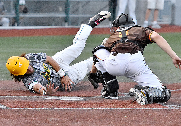 (Brad Davis/The Register-Herald) Miners baserunner Mike Santaromita twists as he dives towards the plate to successfully avoid the tag from Kokomo catcher Colin Butkiewicz to take a 4-2 lead in the 7th off a hustle single by teammate Fernando Ortiz Saturday night at Linda K. Epling Stadium.