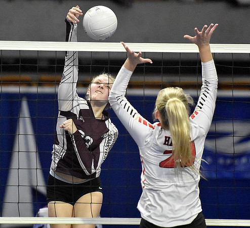 (Brad Davis/The Register-Herald) Woodrow Wilson's Savanna McMillion spikes the ball as University's  Anna Tretheway tries to block during State Volleyball Tournament action Friday evening at the Charleston Civic Center.