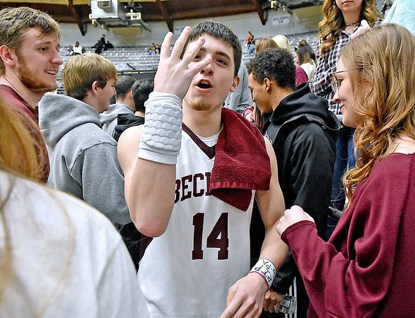 (Brad Davis/The Register-Herald) Woodrow Wilson player Bryce Radford notices the camera and takes the opportunity to remind us all that four more wins will bring home a Class AAA state title as he and teammates greet their classmates in the student section following their Sectional Championship win over Princeton Friday night at the Beckley-Raleigh County Convention Center.