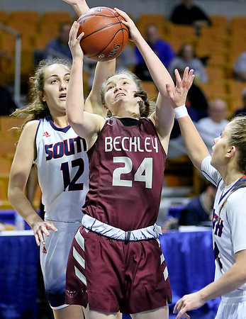 (Brad Davis/The Register-Herald) Woodrow Wilson's Liz Cadle drives and scores as Parkersburg South's Makenna Winans, left, and Devin Hefner defends Wednesday afternoon at the Charleston Civic Center.