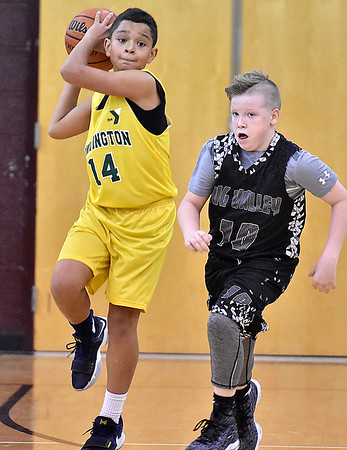 (Brad Davis/The Register-Herald) Huntington Gators player Tayveon Wilson leaps to make a long pass as Tug Valley's Kaden Hale gives chase during the fifth grade Biddy Buddy Championship game Sunday afternoon at Woodrow Wilson High School.