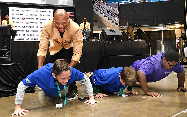 NFL Pro Football Hall of Fame Aeneas Williams, works with three Raleigh County Middle School students doing push-ups during the Youth Summit held at the Beckley-Raleigh Convention Center Friday morning.<br /> (Rick Barbero/The Register-Herald)