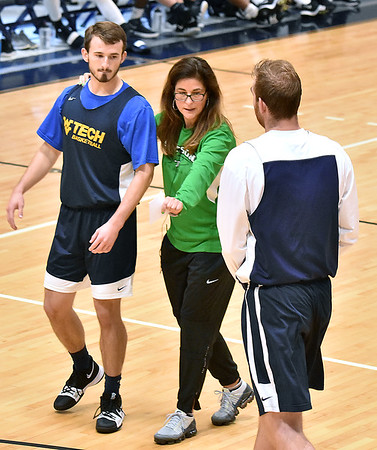 """(Brad Davis/The Register-Herald) Stetson University women's basketball head coach Lynn Bria positions WVU Tech basketball players Cole Schoolcraft, left, and Brent Daniels as she runs demos on a variety of plays that can be run out of the """"Princeton Offense"""" system for other area coaches in attendance for this year's WVU Tech Coaches clinic Sunday morning in the Van Meter Gymnasium."""