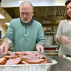 (Brad Davis/The Register-Herald) Church member Donna Cook, right, and lead pastor Steve Hamrick put chopped ham it into pans as they and a crew of fellow members prepare United Methodist Temple's annual Community Christmas Dinner Saturday night inside The Place. As they do every year, United Methodist Temple will utilize an army of volunteers young and old to feed well over 500 people in the area, and anyone is welcome. The dinner begins at 11:00 a.m. at The Place and runs until 2:00 p.m.