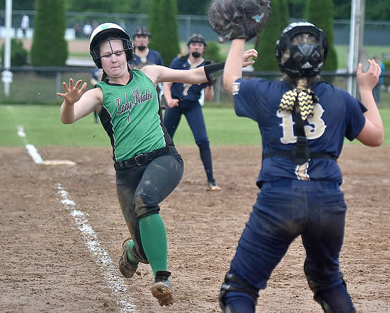 (Brad Davis/The Register-Herald) Fayetteville baserunner Carrie Taylor starts her slide as she charges home to score during the Pirates victory in a wild, 8 inning, 22-14 rain-soaked thriller against Greenbrier West Wednesday night at Huse Park in Fayetteville.