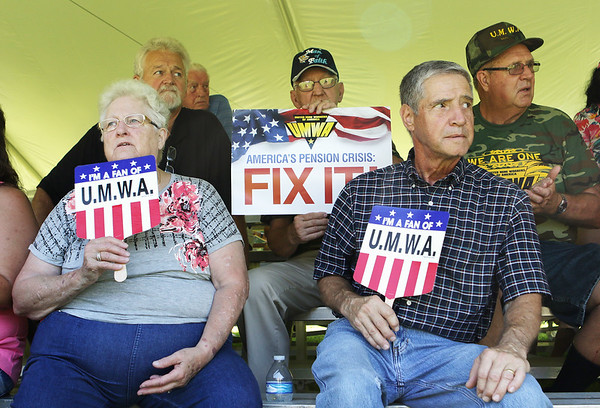 Margaret and Lynn Hayes fan themselves while listening to speeches at the 80th annual UMWA Labor Day celebration in Racine Monday. (Jenny Harnish/The Register-Herald)