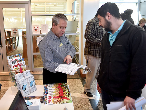 (Brad Davis/The Register-Herald) Joe Guffy with the Beckley-Raleigh County Chamber of Commerce speaks with prospective employee Michael Harvey as he and other job seekers link up with around 137 employers from local and national organizations during a Job and Resource Fair inside the Erma Byrd Higher Education Center Friday afternoon.