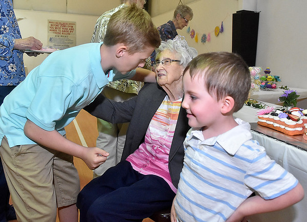 (Brad Davis/The Register-Herald) Lifelong Bradley resident Lula Thompson is all smiles as great great grandsons Brodie (left), 9, and Landrie James, 4, come to give her hugs during her 100th birthday celebration Saturday afternoon at Bradley Free Will Baptist Church.