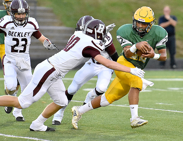 (Brad Davis/The Register-Herald) Greenbrier East ball carrier Jaylon Battaile is chased down by Woodrow Wilson defenders Maddex McMillen (#10) and Jacobe Harville (#15) Friday night in Fairlea.