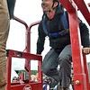 (Brad Davis/The Register-Herald) Denver, Colorado B.A.S.E. jumper Tyler Loeffler climbs into the scissor lift basket as he prepares for an extra high jump during Bridge Day Saturday morning in Fayetteville.