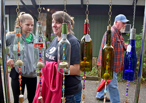 """(Brad Davis/The Register-Herald) Guests pass by a row of old bottles """"reborn"""" into wind chimes by Summersville glass artist Jill Browning Fowler as they browse wares from area artisans during the 31st Annual Cranberry Shindig Sunday afternoon at the Cranberry Nature Center in Hillsboro."""