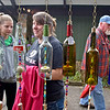"(Brad Davis/The Register-Herald) Guests pass by a row of old bottles ""reborn"" into wind chimes by Summersville glass artist Jill Browning Fowler as they browse wares from area artisans during the 31st Annual Cranberry Shindig Sunday afternoon at the Cranberry Nature Center in Hillsboro."