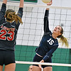 (Brad Davis/The Register-Herald) Meadow Bridge's #15 leaps to spike the ball as Liberty's Madison Maynard steps up to try and block it Wednesday night in Fayetteville.