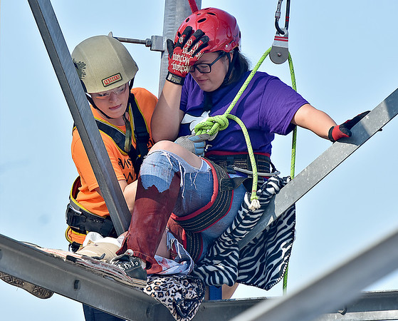 (Brad Davis/The Register-Herald) Volunteer Alexis Franklin, right, plays the role of a frieghtened and badly injured worker high atop a cell phone tower as trainees from Team WV Wild Med are tasked with reaching, treating and rescuing her during a high intensity, scenario-based simulation that was part of the annual Battle in the Gorge E.M.S. and Fire Competition Sunday morning on the grounds of Fayette County 911. Participating teams compete and train in scenarios that test both individual and combined rescue disciplines such as vertical rescue, paramedic, basic EMT and vehicle extrication. Teams don't know what scenario they will be thrown into until they arrive on the scene.