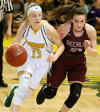 (Brad Davis/The Register-Herald) Greenbrier East's Autumn Hill drives up the court as Woodrow Wilson defender Cloey Frantz keeps pace Saturday night in Fairlea.