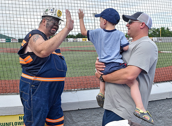 (Brad Davis/The Register-Herald) Dad Josh holds three-year-old Jasper Birchfield as he gets a high five from West Virginia Miners mascot Big Paul prior to the start of the team's season opener against the Kokomo Jackrabbits Wednesday evening at Linda K. Epling Stadium. It was young Jasper's first ever baseball game.