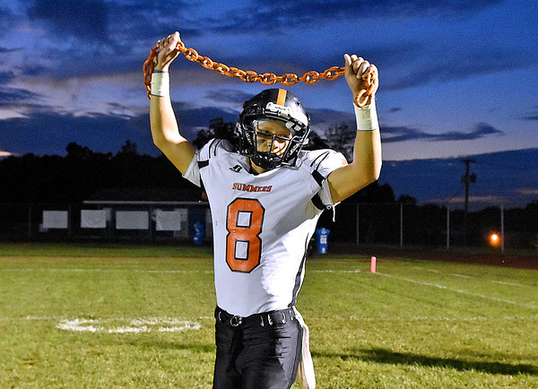 (Brad Davis/The Register-Herald) Summers County's Sam Wykle holds up a chain as he prepares to lead his teammates onto the field for a road game at Indy Friday night in Coal City.