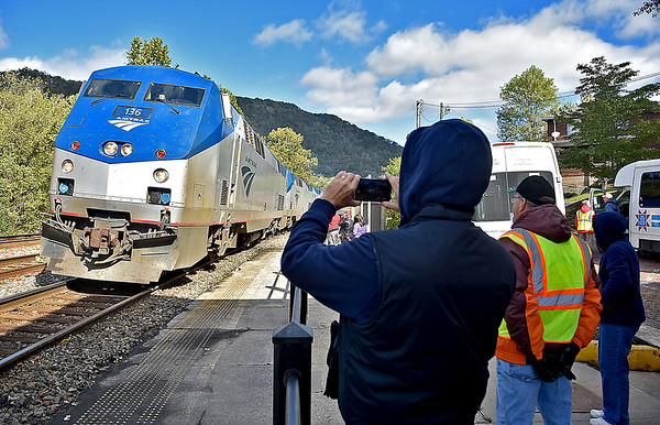 (Brad Davis/The Register-Herald) Denver, Pennsylania resident Dean Reonieri positions his smartphone to record the arrival of the New River Train Excursion at the historic Hinton train depot during Railroad Days Sunday afternoon. His wife Debra, far lower right, and volunteer Mark Patton (safety vest), watch the arrival beside him.