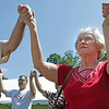 Rosemary Wills holds hands with others while listening to UMWA International President Cecil Roberts' speech at the 80th annual UMWA Labor Day celebration in Racine Monday. Wills' husband is a retired and injured coal miner. (Jenny Harnish/The Register-Herald)