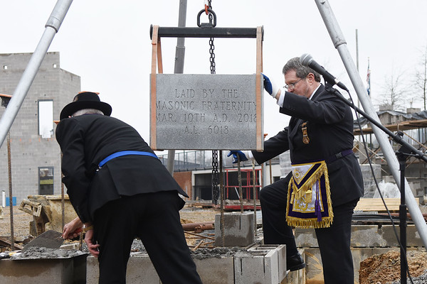 Carl McDaniel, left, Grand Master of the West Virginia Masons, and Richard Nuhfer, past Grand Master, work to set into place the Masonic cornerstone to the new Beckley Police Department Building in Beckley on Saturday. The Masons haven't set a cornerstone in Raleigh County in more than 50 years. (Chris Jackson/The Register-Herald)