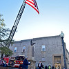 (Brad Davis/The Register-Herald) A massive American flag hangs from the extended ladder of a Mt. Hope fire truck as resident Brenda Troitino leads the town's annual Veteran's Day ceremony in front of the War Memorial on Main Street Sunday afternoon.