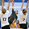 (Brad Davis/The Register-Herald) WVU Tech's Katelyn Byrd rips a spike between Midway defenders Candi Staten, left, and Madi Eberst Saturday afternoon in the Van Meter Gymnasium.