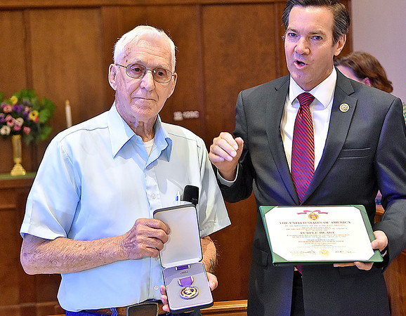 (Brad Davis/The Register-Herald) Fairdale resident and retired Army Private Howard Collins, a Korean War veteran who was wounded there in February 1952, finally receives his Purple Heart from U.S. congressman Evan Jenkins during a ceremony at the Beckley V.A. Medical Center Saturday morning. Collins was shot in the hand while serving with the 35th Infantry Regiment, 25th Infantry Division. That same bullet also grazed his head.