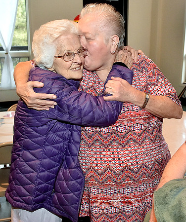 (Brad Davis/The Register-Herald) Ghent resident Florence Mandakunis, left, is greeted with a big hug and a smooch by her close friend Carol Murphy during the opening moments of her 100th birthday party Saturday afternoon at Calvary Assembly of God.