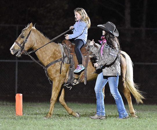 (Brad Davis/The Register-Herald) Eight-year-old Greenlea Price gets the chance to go for a horse ride with guidance from veteran equestrian and Indy senior Madison Deck during the lighting delay Friday night in Coal City. Price said it was just her third time riding horses.