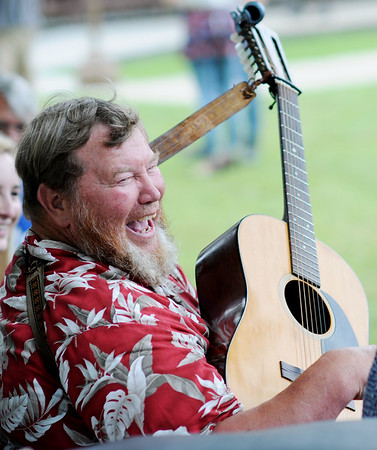 """Fred """"Tomato Freddie"""" Swedberg, from Orange, Mass., laughs as he sings and plays guitar with a group of musicians during the 2018 Appalachain String Band Festival in Clifftop on Wednesday. (Chris Jackson/The Register-Herald)"""