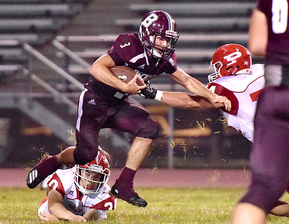 (Brad Davis/The Register-Herald) Woodrow Wilson quarteback Peyton Shehan carries the ball as Parkersburg defenders Brandon Braham, left, and Gage Fiore try to bring him down Friday night in Beckley.