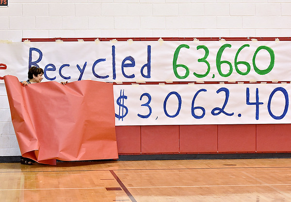 (Brad Davis/The Register-Herald) Sherrie Hunter, Director of Education at the Raleigh County Solid Waste Authority, pulls back a paper cover revealing the total dollar amount earned by Trap Hill Middle School, this year's champion in the annual School Recycling Program, during a ceremony at the school Wednesday afternoon in Glen Daniel. The total includes a $2,000 bonus awarded to Trap Hill for beating out 35 other area schools with the highest percentage grade of total materials recycled at 163%. The figure of 63,660 is the poundage total of all the paper and cardboard the school recycled.