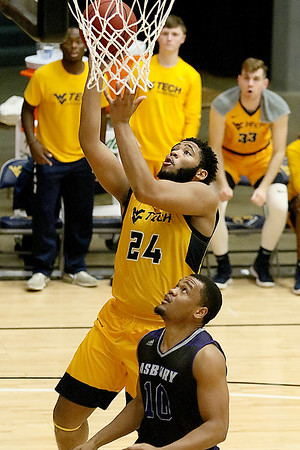 (Brad Davis/The Register-Herald) WVU Tech's Tamon Scruggs drives and scores as Asbury's Dave McCorvey watches during a comeback victory Wednesday night at the Beckley-Raleigh County Convention Center.