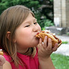 Hannah Barkley, 7, enjoys a hot dog at Dave's Hot Dogs in Renick. Hannah and her mother visit Dave every weekend during the summer for lunch. (Jenny Harnish/The Register-Herald)