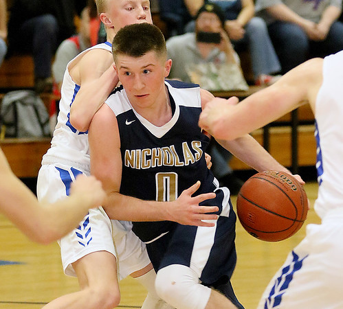 (Brad Davis/The Register-Herald) Nicholas County's Luke LeRose drives and scores as Midland Trail's Austin Isaacs defends Wednesday night in Hico.