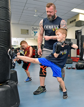 (Brad Davis/The Register-Herald) Seven-year-old Gabriel Jesse works on kicks as dad and instructor Jamie Jesse encourages him during the first Kids Combat Cardio session to be held Sunday afternoon at the YMCA of Southern West Virginia. The one hour class will be held every Sunday in two age groups, kids 5-10 at 3:00 p.m., kids 11-18 at 4:00 p.m. and combines a fun workout environment with basic mixed martial arts training and techniques.