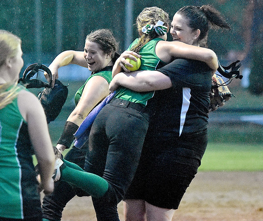 (Brad Davis/The Register-Herald) Fayetteville head coach Morgan Wheeler embraces starting pitcher Ashley Fridley as the Lady Pirates celebrate a victory after a wild, 8 inning, 22-14 rain-soaked thriller against Greenbrier West Wednesday night at Huse Park in Fayetteville.