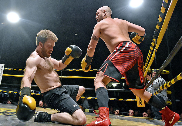 "(Brad Davis/The Register-Herald) Geoff Illes, right, scores a knockdown on opponent Kenneth Jackson after connecting with a heavy right hook during their match in the ""Original"" Toughman Contest Saturday night at the Beckley-Raleigh County Convention Center."