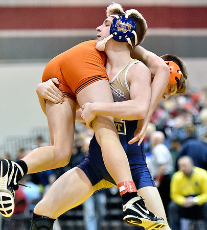 (Brad Davis/The Register-Herald) Greenbrier West's Eric Crowe takes on Wirt County's A.J. Garrett in a 120-pound weight class matchup during state wrestling tournament action Thursday night at Huntington's Big Sandy Arena. West's Crowe won the match.
