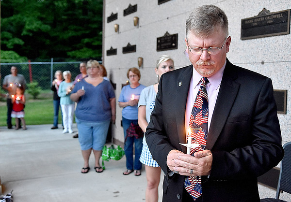 (Brad Davis/The Register-Herald) Scott Lester, Pastor at Gatewood Brethren Church, observes a moment of silence during the closing moments of a Memorial Day Community Candlelight Vigil Sunday night at Huse Memorial Park and Mausoleum.