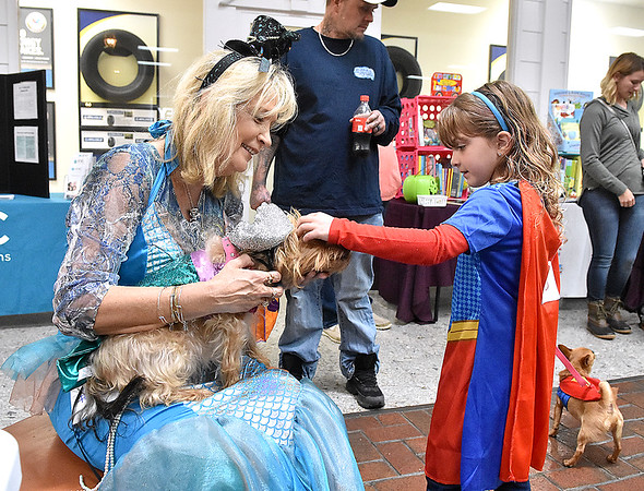 (Brad Davis/The Register-Herald) Seven-year-old Jaylee Rood comes over to meet mermaid pair Bobbi Harvey and her dog Ashley during the Humane Society of Raleigh County's Howloween event Saturday afternoon inside the Beckley Plaza Mall.