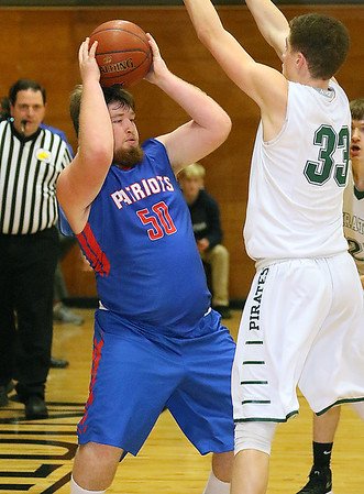 (Brad Davis/The Register-Herald) Midland Trail's Trevor Harrell looks for open teammate after collecting an offensive rebound as Fayetteville defender Jonathan Malay defends Friday night at the Soldiers & Sailors Memorial Building.