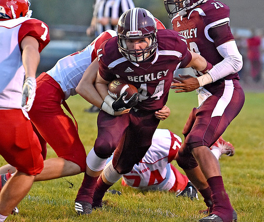 (Brad Davis/The Register-Herald) Woodrow Wilson's Nicholas Wickline rumbles through the line as Parkersburg defender Jacob Woodyard tries to bring him down Friday night in Beckley.