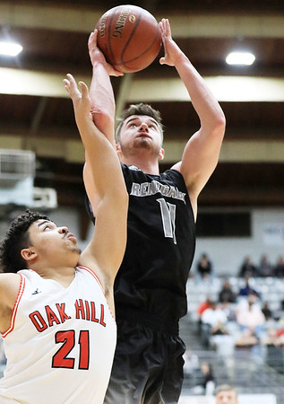 Westside's Elijah Puett (11) is fouled ob a shot by Oak Hill's (21) Dietrick Penn (21) during the first half of their basketball sectional championship Thursday in Beckley. (Chris Jackson/The Register-Herald)