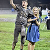 (Brad Davis/The Register-Herald) Muddy Meadow Bridge senior Lukas Stephens reacts to being named this year's Mr. Wildcat as escort Isabelle Newman, also a senior, looks on in still-clean clothes Friday night in Meadow Bridge.