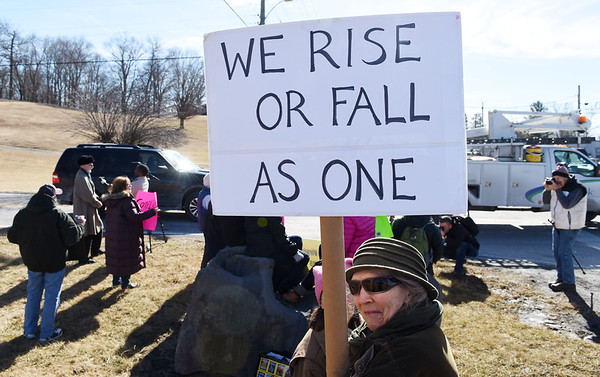 """Carli Mareneck, from Monroe County, holds a sign that reads """"We Rise Or Fall As One"""" along Rt. 219 at the entrance to the Lewisburg Airport prior to the Republican Party's retreat at the The Greenbrier Resort in White Sulphur Springs on Wednesday. """"I feel like the reason I show up to these things is to protect even the leaders that are doing bad things,"""" she said. """"Because I think that they are blind. They do not realize that by derugulating industry that will cause so much pollution that their own families won't be able to survivie. If I'm protecting water for myself, than I'm protecting water for them as well. If they have this sucicdal urge, they shouldn't take the rest of us with them. West Virginia is probably pone of the only states hat has prestine water left."""" (Chris Jackson/The Register-Herald)"""