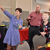 (Brad Davis/The Register-Herald) Daughter Barbara Sharer, left, and owner Tim Harper join longtime Plaza McDonald's employee Jessie Wolfe as they watch a slideshow during her retirement party September 19 at Black Knight.
