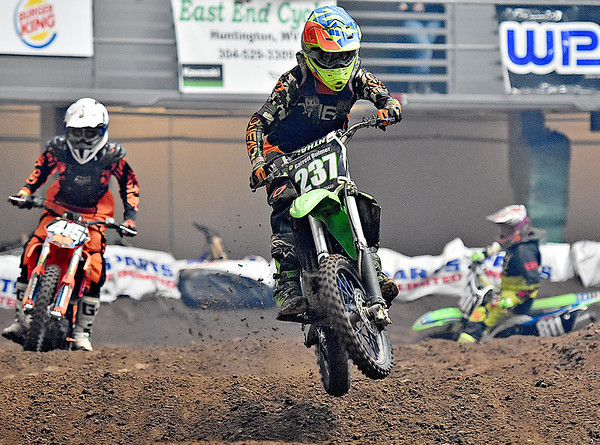 "(Brad Davis/The Register-Herald) 15-year-old racer Garrett Bulmer (middle, hometown unspecified) skips through the ""whoops"" section of the course during the weekend's Tristate MX dirt bike racing event Saturday night at the Beckley-Raleigh County Convention Center."